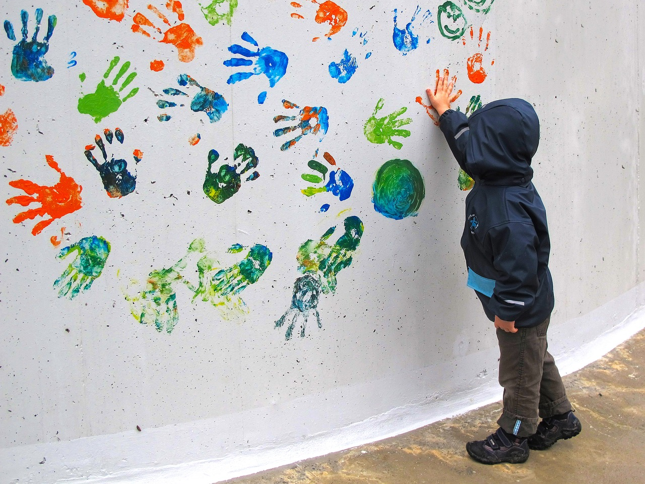 Child hand panting on white wall