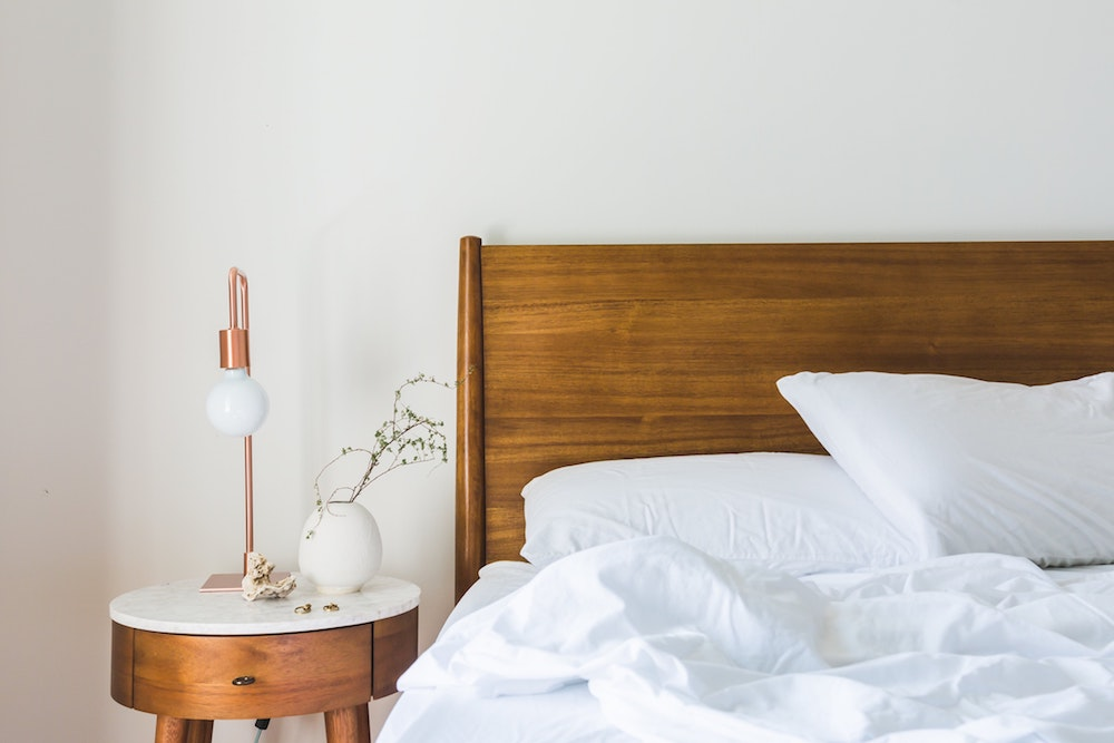 Crisp white sheets with rose gold side lamp